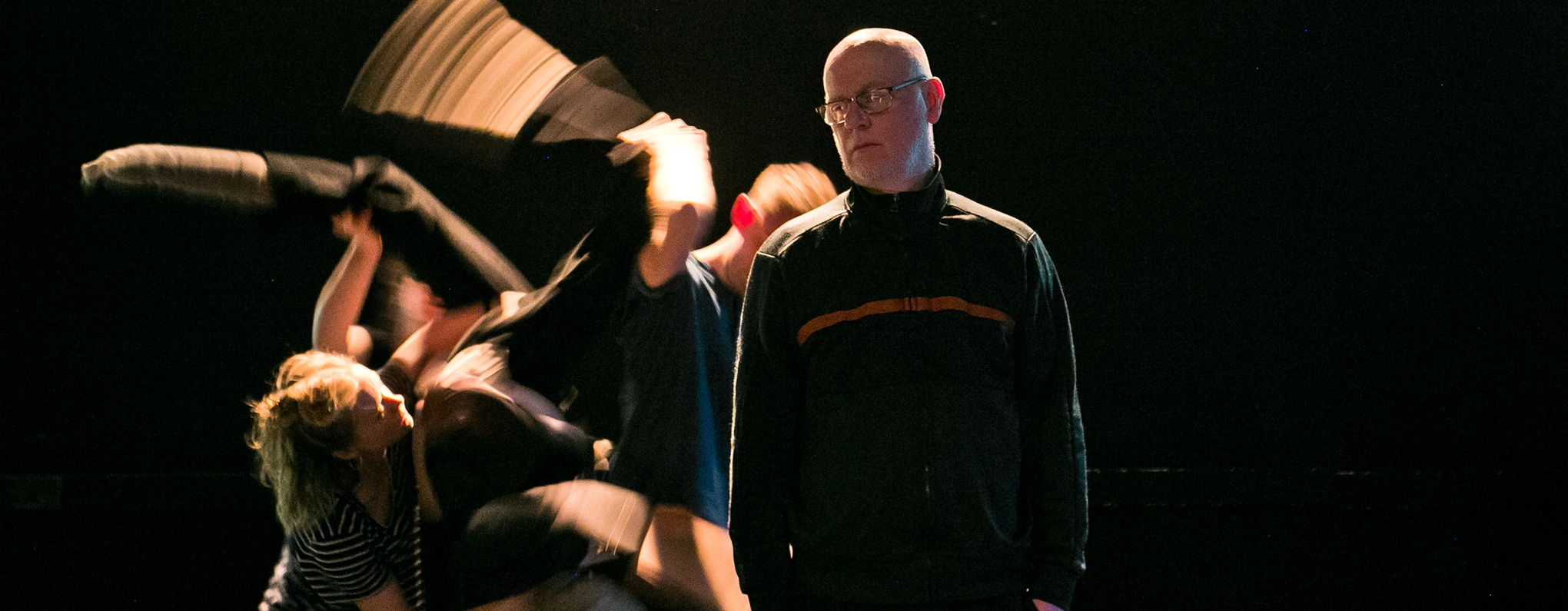 Stationary actor on dark stage with dancers behind.