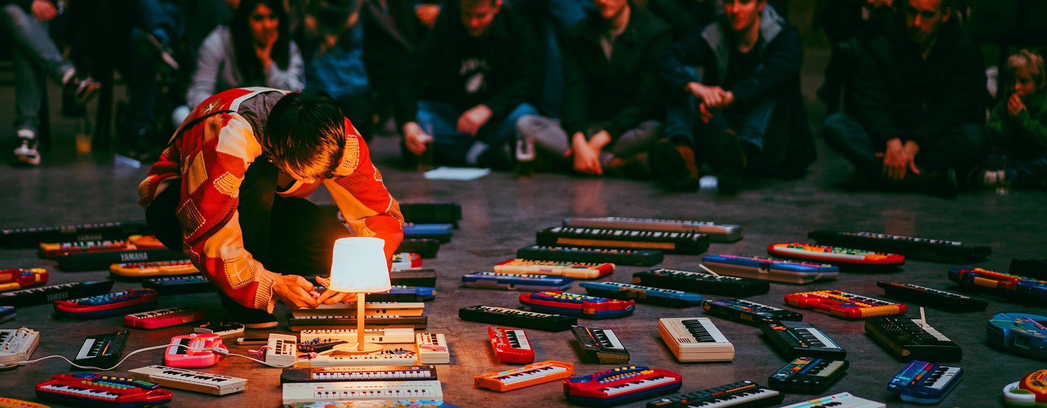 Artist crouching on floor surrounded by dozens of mini keyboards.