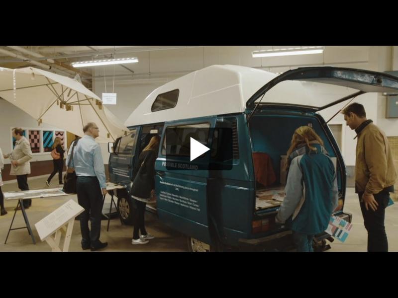 People in a gallery looking at a vintage campervan.